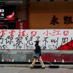 A man walks past graffiti sprayed by protesters on a wall in Hong Kong, China, Dec 9. — Reuters