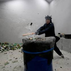 A customer wearing protective gear smashes a wine bottle in an anger room in Beijing, China January 12, 2019. Picture taken Jan 12, 2019. — Reuters