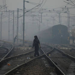 A woman crosses a railway line on a smoggy morning in New Delhi, India, today. — Bernam