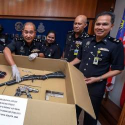 Kelantan Deputy Police Chief SAC Abdullah Mohammad Piah (c) displays a shotgun and a homemade pistol, seized during a raid in Kampung Padang Mokkan, at a press conference at the Kelantan police headquarters today. - Bernama