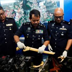 Pahang Criminal Investigations Department chief Datuk Othman Nayan (c) and other officers display items seized after a raid and the apprehending of 'Geng Rahman' at a press conference in at the Kuantan police headquarters today. - Bernama