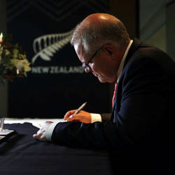 Australian Prime Minister's Office shows Prime Minister Scott Morrison writing a message in a condolence book at the New Zealand High Commission in Canberra — AFP