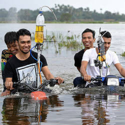 Ikram Shahidi Mat Kail, 24, (right) and his brother, Muhammad Zakaria, 22, (left) riding their modified bicycles through a flooded area in Kampung Banggol yesterday. — Bernama