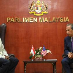 Home Minister Tan Sri Muhyiddin Yassin (R) talked with his colleague Singapore Law and Home Minister K. Shanmugam at Parliament yesterday. - Bernama