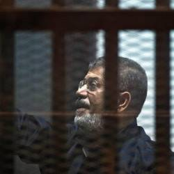 Egypt's ousted Islamist president Mohamed Morsi stands behind the bars during his trial in Cairo on June 16, 2015. — AFP