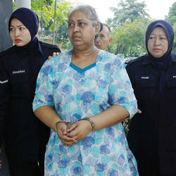 M. A. S. Ambika, the accused in the case, is accompanied by policewomen. The picture was taken on Feb 10, 2018. — BBXpress