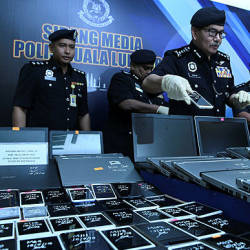 City police chief Datuk Seri Mazlan Lazim inspecting a portion of the seized good at a press conference in the Kuala Lumpur Police Contingent Headquartes today.