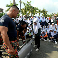 Firemen help Nadira Ahmad, 16, a student, to use a rescue device on a car door at the closing ceremony of the 'Abang Bomba Ke Sekolah' at SMK Taman Kota Masai 2 today.