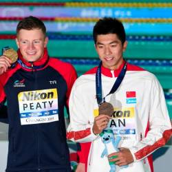 (L-R) Silver medallist Britain's James Wilby, gold medallist Britain's Adam Peaty and bronze medallist China's Yan Zibei celebrate during the medals ceremony after the final of the men's 100m breaststroke event during the swimming competition at the 2019 World Championships at Nambu University Municipal Aquatics Center in Gwangju, South Korea, on July 22, 2019. — AFP