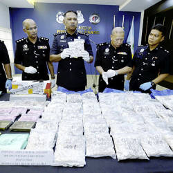 Penang police chief Datuk T. Narenasagaran (center) holding one of the packets of heroin seized.