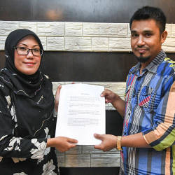 Majdah Muhamad (L) who is representing Tengku Amalin A'ishah Putri receive the letter of apology from Shaiful Afzan Mahamed, on Oct 21, 2019. — Bernama