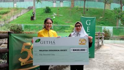 From left: Tan hands over the mock cheque to Linda at Zoo Negara.
