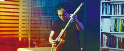 Azmyl playing the electric guitar in the Penghasut Blues music video.