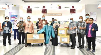 Mohd Shukri (fifth from left) presenting the PPE to a representative of Hospital Shah Alam.