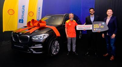 Shairan (left) and BonusKad Loyalty Sdn Bhd CEO Melvin Ooi (right) presenting the BMW X3 to Neeraj yesterday.