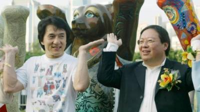 Former Hong Kong home affairs secretary Patrick Ho Chi Ping (R), pictured in a 2003 photograph with movie star Jackie Chan, has been convicted over a bribery scheme. — AFP