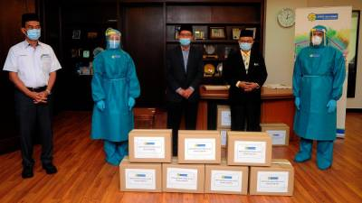 MAIS chairman Datuk Mohammed Khusrin Munawi (C) and Selangor Health Director Datuk Dr Sha'ari Ngadiman (2nd from R) and LZS CEO Saipolyazan M Yusop (L) show off a contribution of 2,000 PPE. - Bernama