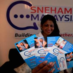 Founder and president of Sneham Malaysia Welfare Association Dr Florance Sinniah holds up some pamphlets at the Sneham Center in Butterworth today. - Bernama