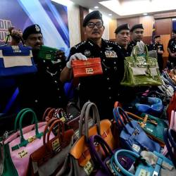 Kuala Lumpur police chief Datuk Seri Mazlan Lazim (c) displays the luxury brand handbags that were seized at a press conference, at the Kuala Lumpur police headquarters today. - Bernama