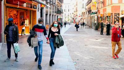 A couple wear protective face masks as they walk in unusually quiet Postas street in central Madrid, Spain, March 13, 2020. -Reuters