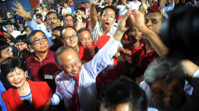 Photo shows Singaporean presidential candidate Tan Cheng Bock (2L) greeting his supporters as he waits for the results of the presidential elections at Jurong east Stadium in Singapore.
