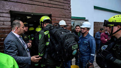 Firefighters work at the scene of a car bomb attack in a police academy in Bogota that left at least nine people dead and 54 injured. — AFP