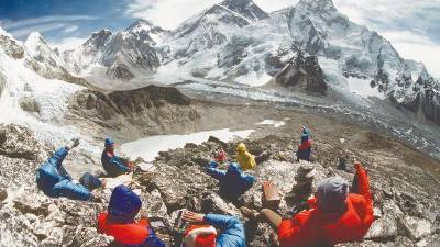 A group of tourists enjoy the view of the Everest from the Kala Patthar landmark peak.