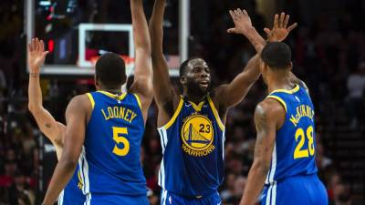 Golden State Warriors forward Draymond Green (23) gives high-fives to teammates center Kevon Looney (5) and forward Alfonzo McKinnie (28) during the second half in game three of the Western conference finals of the 2019 NBA Playoffs at Moda Center. - Reuters