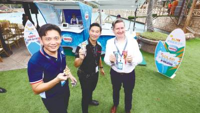 (Clockwise, from R) Teo, Ho and Mayer enjoying an ice-cream treat at the launch of Nestle's solar-powered ice-cream kiosk. – NESTLE MALAYSIA