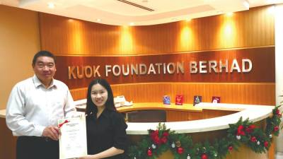Kuok Foundation general manager Ng presents a scholarship to a recipient, Lim.