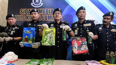 Kuala Lumpur police chief Comm Datuk Seri Mazlan Lazim (C) reveals items seized after a press conference on 'Black Money' fraud syndicates at the Kuala Lumpur police headquarters today. — Bernama