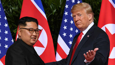 Photo shows US President Donald Trump (R) gestures as he meets with North Korea's leader Kim Jong Un (L) at the start of their historic US-North Korea summit, at the Capella Hotel on Sentosa island in Singapore. — AFP