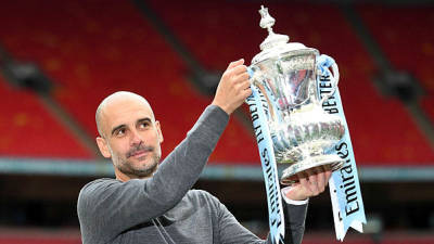 Manchester City's Spanish manager Pep Guardiola holds the winner's trophy as the team celebrates victory after the English FA Cup final football match between Manchester City and Watford at Wembley Stadium in London, on May 18, 2019. - AFP