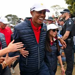 US team captain Tiger Woods (C) celebrates with girlfriend Erica Herman after the US won the Presidents Cup golf tournament on the final day in Melbourne on Dec 15. — AFP