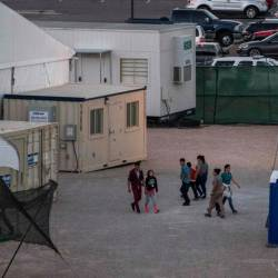 In this file photo taken on June 21, 2019 Immigrants are pictured behind the fences of a temporary facility set up to hold them at the El Paso Border Patrol Station. - AFP