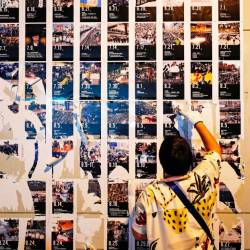 A pro-China supporter cleans up 'Lennon Walls' of anti-government posters and memo notes outside Yuen Long MTR station in Hong Kong, China Sept 21, 2019. - Reuters
