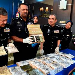Penang police chief Datuk T. Narenasagaran (2nd from L) along with his officers display the ammunition and drugs seized after a raid on a drug-processing syndicate, during a press conference at the Penang police headquarters in George Town today. - Bernama