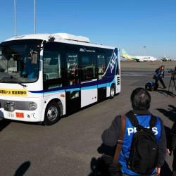Journalists look at a driverless bus during an open test drive demonstration at Tokyo's Haneda International Airport on Jan 22, 2019. — AFP