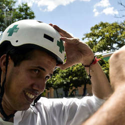 "Venezuelan opposition leader and self declared acting president Juan Guaido wears a Green Cross helmet as he posses for a picture with volunteers of the movement ""Aid and Freedom Venezuela Coalition"" after delivering a speech in Caracas — AFP"