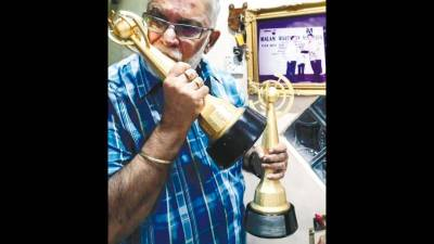 WHAT A RIDE ... Former TV personality Datuk Karam Singh Walia kisses one of his two 'Anugerah Seri Angkasa' award. — Sunpix by Ashraf Shamsul