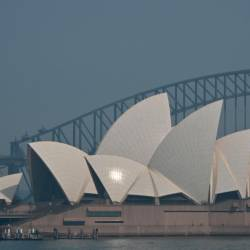 The Sydney Opera House and Harbour Bridge are seen through a smokey haze which blankets Sydney on Nov 21. — AFP