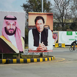 A foreigner rides past billboards showing portraits of Saudi Arabian Crown Prince Mohammed bin Salman (L) and Pakistan's Prime Minister Imran Khan (R) and a banner welcoming the prince ahead of his arrival in Islamabad on Feb 15, 2019. — AFP