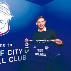 Cardiff City's new signing Argentinian striker Emiliano Sala holds the team's jersey after his unveiling.