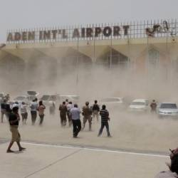 People seek cover from rising dust as a Qatari military cargo plane carrying aid lands at the international airport of Yemen's southern port city of Aden Aug 1, 2015. — Reuters