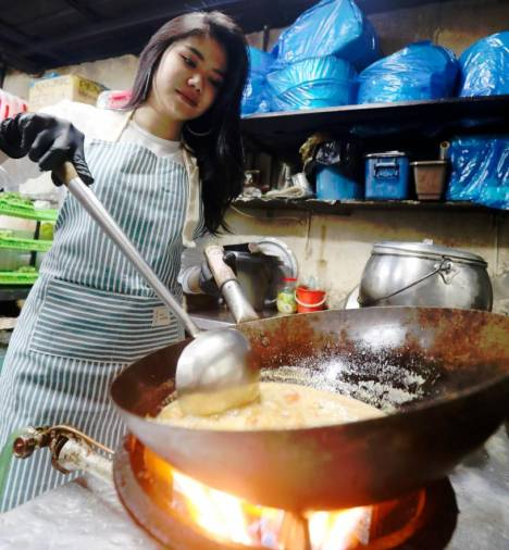 Nadiah working the wok at the restaurant. – MASRY CHE ANI/THESUN