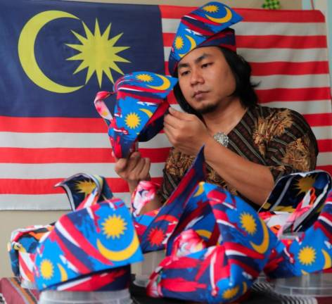 Tanjak maker Muhd Ashraf Mohd Saad putting a final touch on the traditional tanjak that he made for order . The tanjak notice is based on Malaysian flags in conjunction with the 63rd independent day at his apartment in Saujana Height,Teluk Kumbar. MASRY CHE ANI/THE SUN