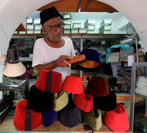 COLOURFUL HEADWEAR... A trader dusting off a songkok at his shop in Jalan Lebuh King in George Town that offers traditional as well as Pakistani and other songkok varieties ranging from RM20 to RM35. MASRY CHE ANI/THE SUN