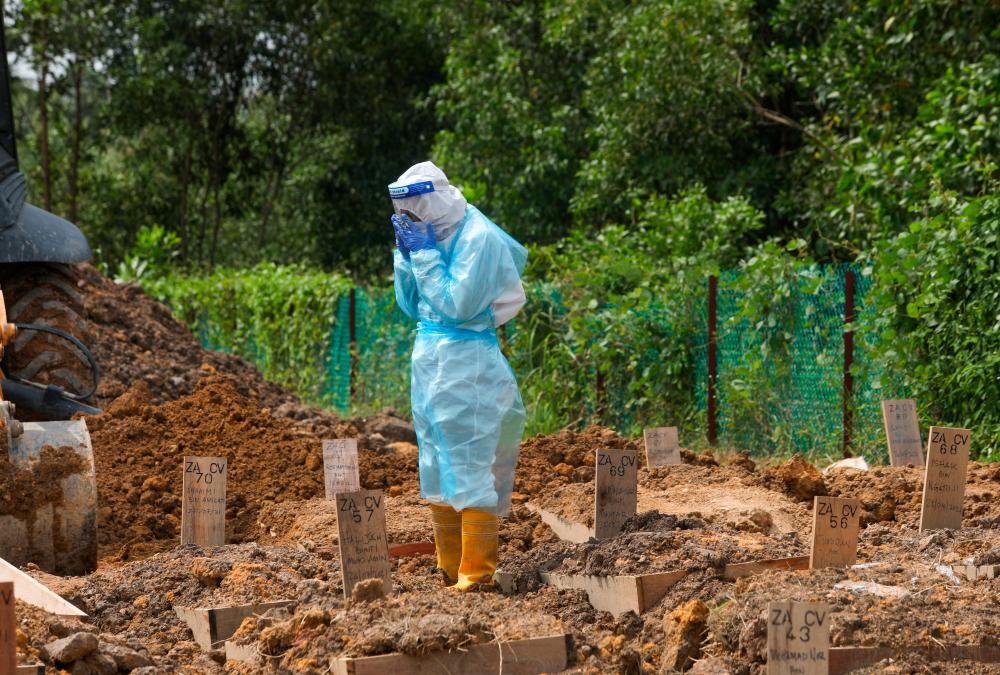 A cemetery worker wearing protective suits praying for a Covid-19 victim during a burial at Tanah Perkuburan Islam Selat Klang. -ASYRAF RASID/ THESUN