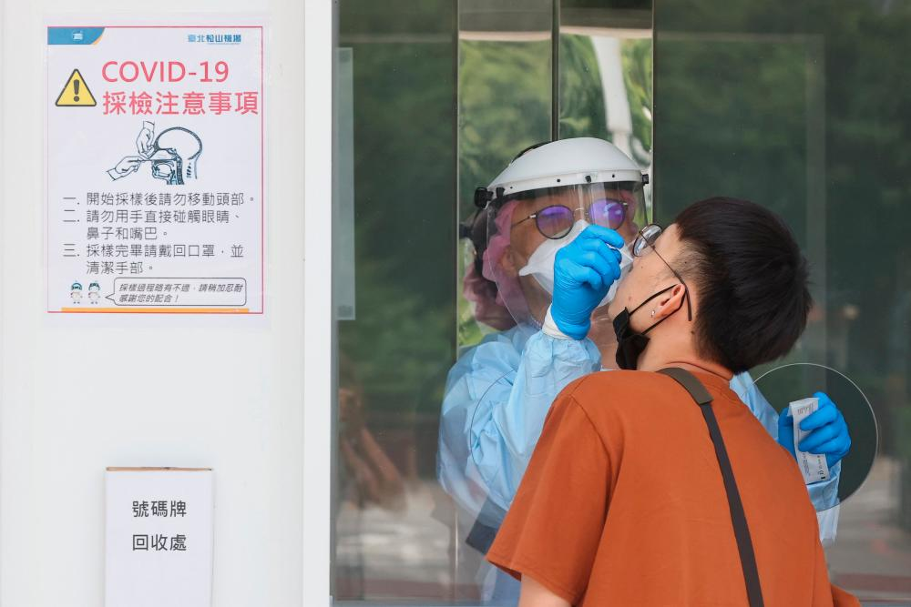 A medical worker conducts a rapid test for coronavirus disease (Covid-19) on a Taiwanese resident following an increasing number of locally transmitted cases at Songshan Airport in Taipei, Taiwan, June 2, 2021. -REUTERSPix