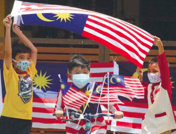 PATRIOTIC SPIRIT... Haifal Yusri (centre) with friends Ridhuan Hakimi (right) and Abdul Rahman waving the Jalur Gemilang near their homes in Kepala Batas, Penang ahead of Merdeka Day on Aug 31. The theme for this year's celebration is 'Malaysia Cares'. MASRY CHE ANI/THE SUN